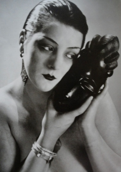 Noire et blanche (variante). Kiki torse nu de face portant un masque africain contre son visage. Man Ray, 1926